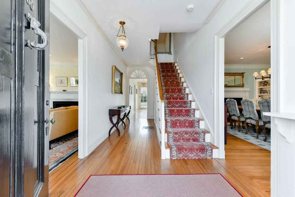 A large entry foyer with a staircase and rooms off it.