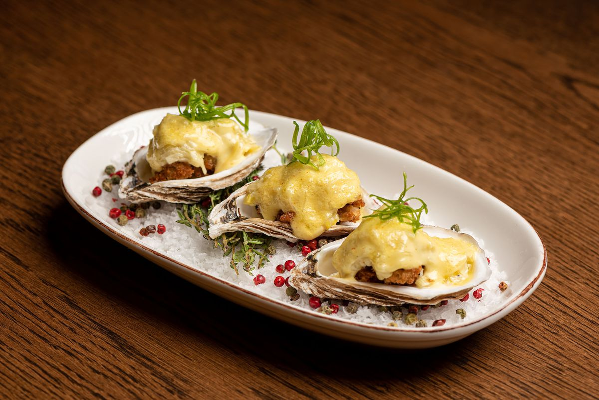 A trio of oysters with yellow sauce on top.