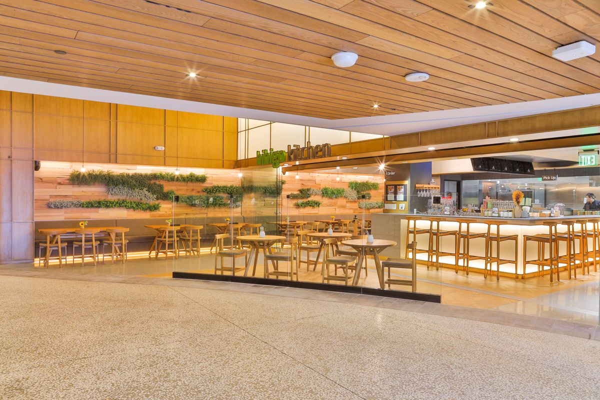 A brightly lit subterranean restaurant space with blonde wood in a mall.