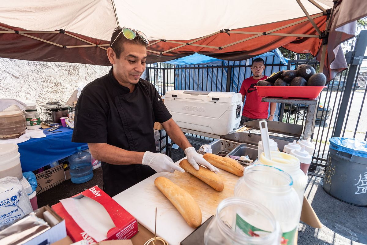 A street food chef cuts open a long loaf of bread under a tent.