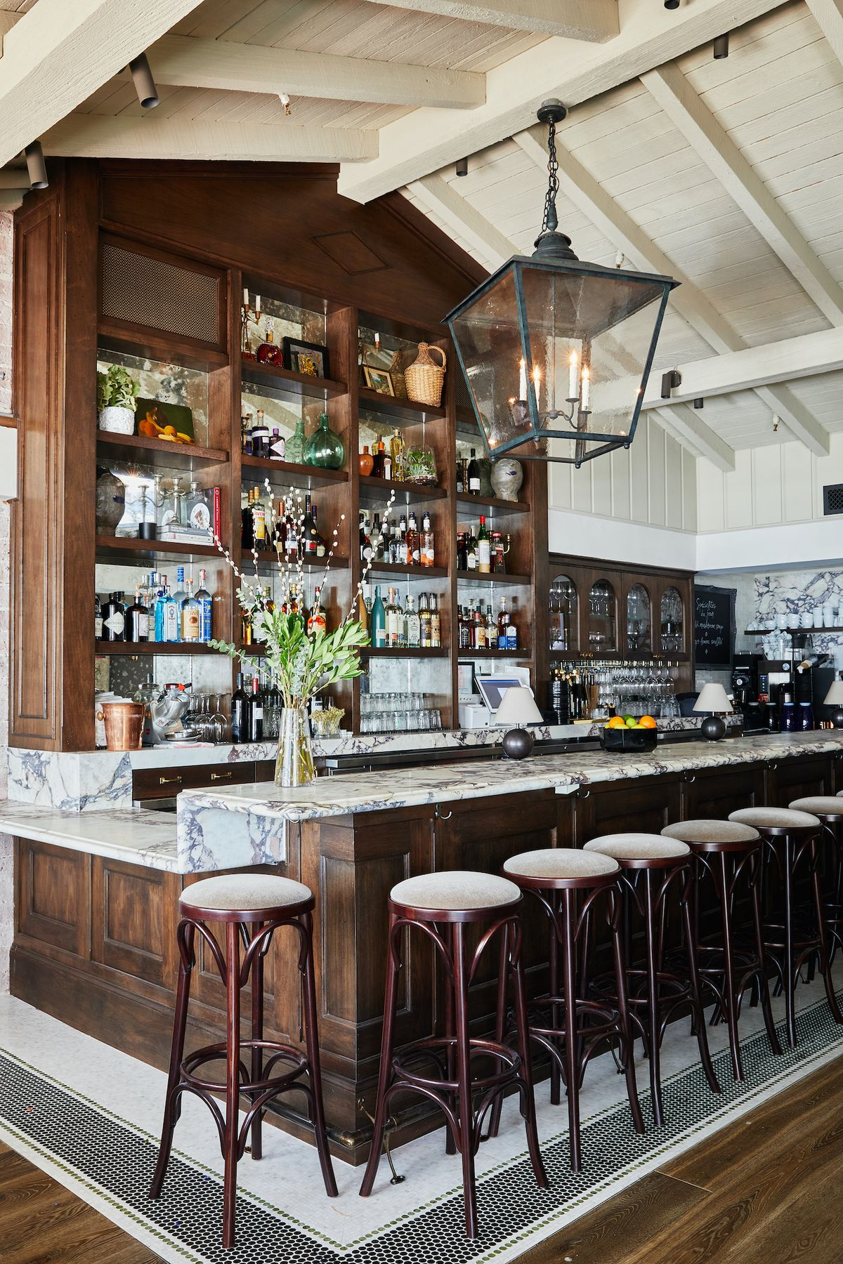 A tall ceiling and wooden bar area inside a French restaurant with light streaming in.