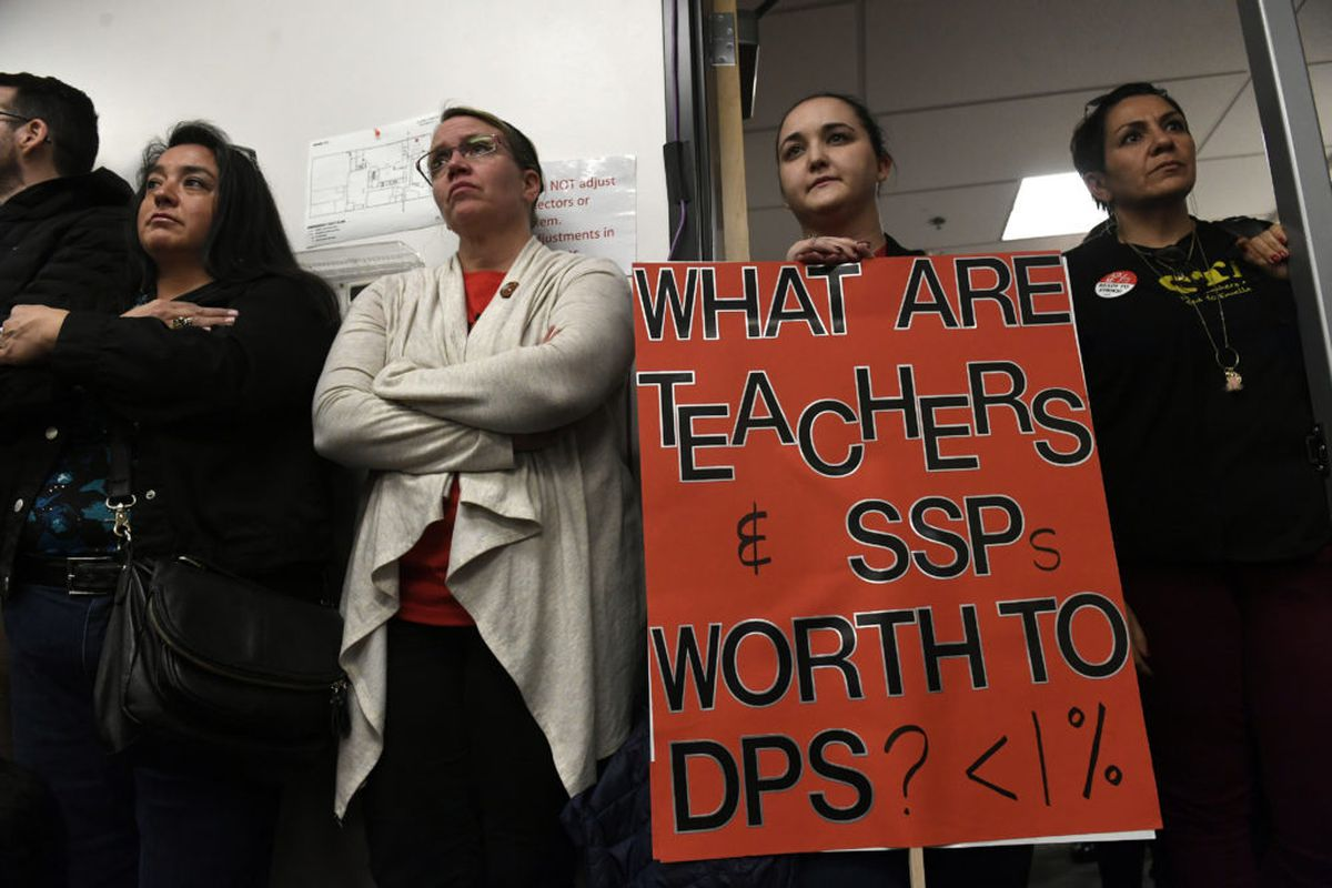 Jennifer Holtzmann, second from right, holds a protest sign during continued negotiations between DPS teachers and administrators.