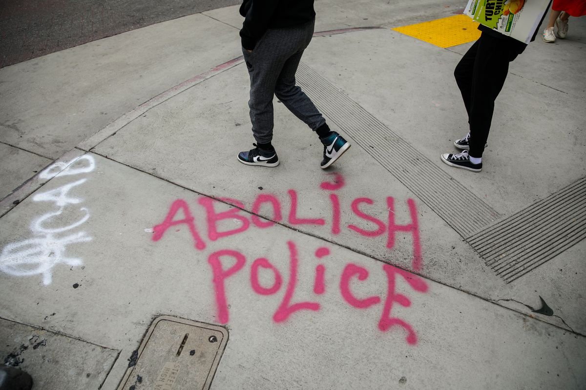 "The spray-painted words ""abolish police"" on a Los Angeles sidewalk."