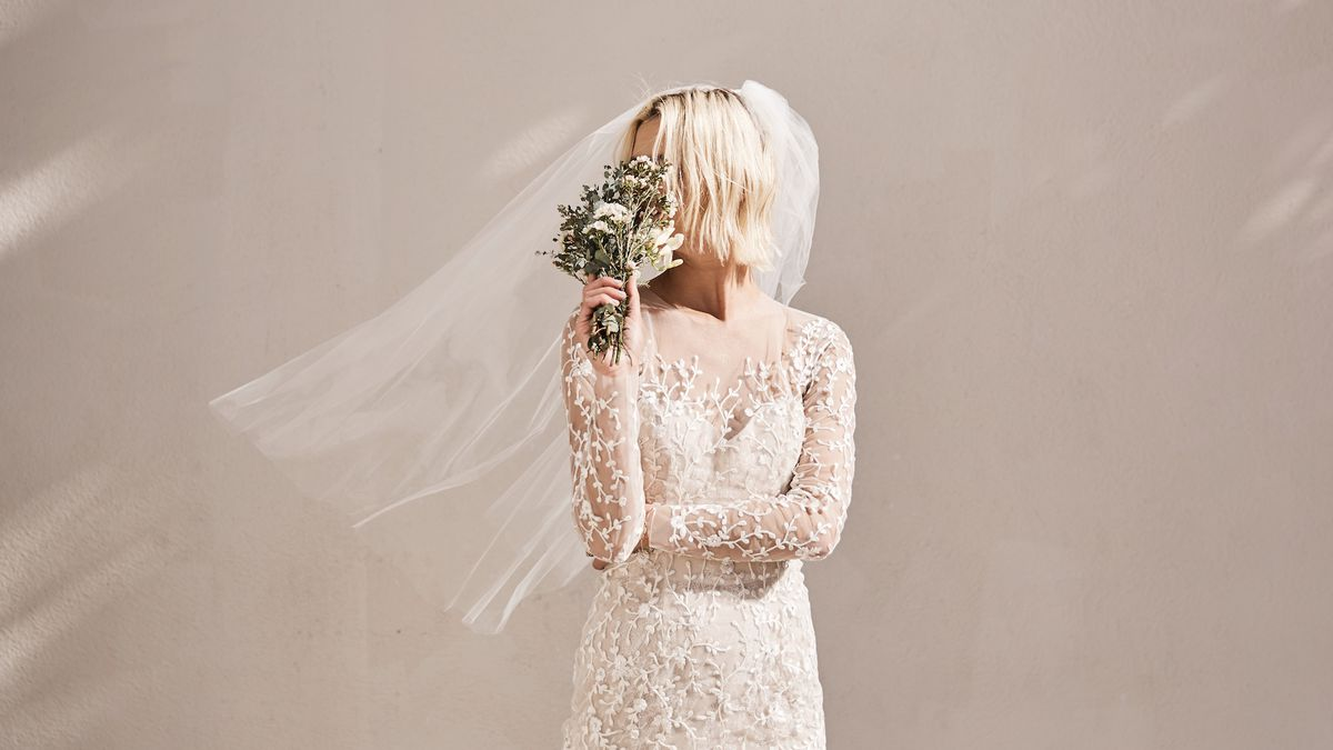 A model in a beaded long-sleeve wedding gown and veil, with flowers