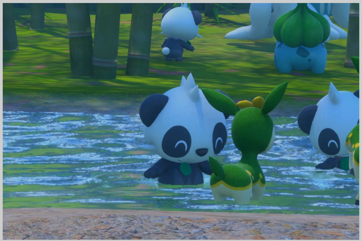 A Pancham happily plays in a river with some Deerling