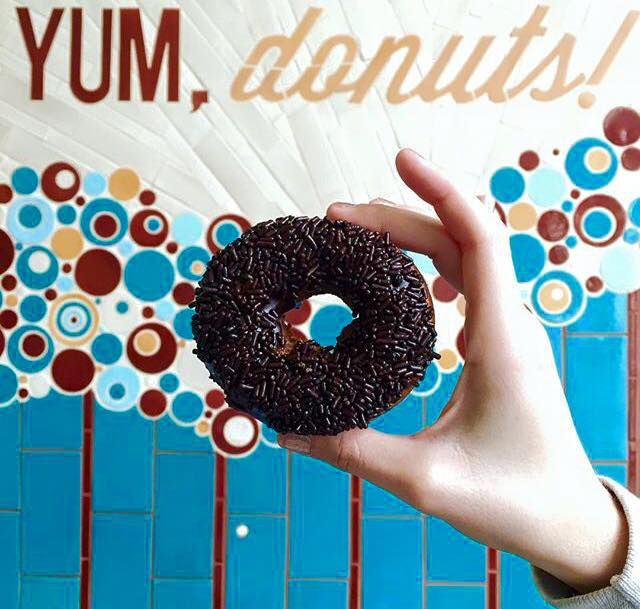 """A hand holds a chocolate frosting and sprinkle topped doughnut in front of a sign that says, """"Yum, donuts!"""""""