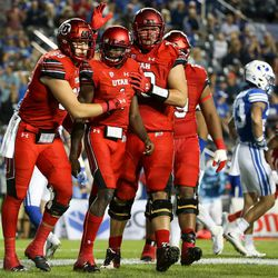 Utah Utes tight end Harrison Handley (88), quarterback Tyler Huntley (1) and offensive lineman Jackson Barton (70) celebrate after Huntley ran for a touchdown, putting the Utes up 16-0 over the Brigham Young Cougars in the third quarter at LaVell Edwards Stadium in Provo on Saturday, Sept. 9, 2017.