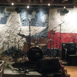A Texas flag made from reclaimed denim and bandanas serves as backdrop for musical acts in the boot bar.