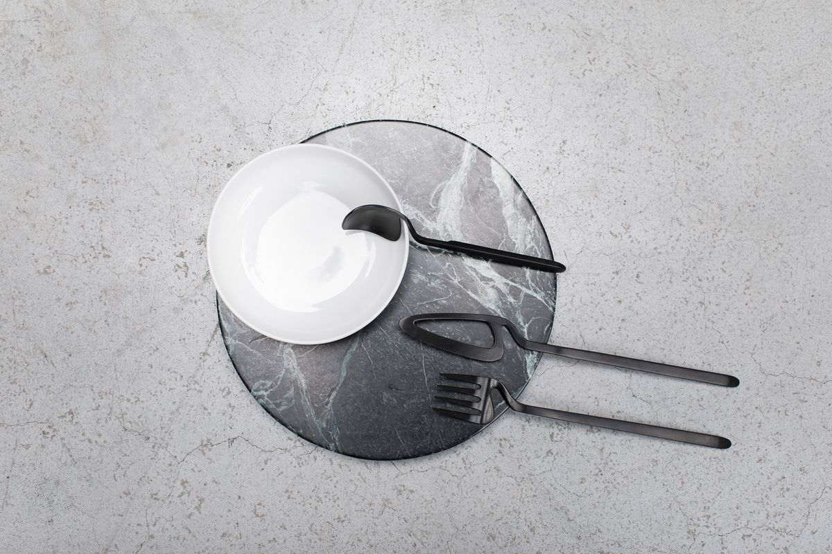 Spoon hanging on the side of a bowl