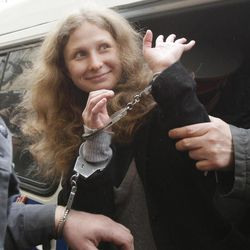 """Maria Alyokhina of Pussy Riot is escorted to a courtroom in Moscow, Russia, Thursday, April 19, 2012. Five members of the band Pussy Riot briefly seized the pulpit of Moscow's Christ the Savior Cathedral in February to chant """"Mother Mary, drive Putin away."""" Moscow court is set to consider extending the detention of three female punk rockers arrested after a surprise protest performance inside the country's main Orthodox cathedral."""