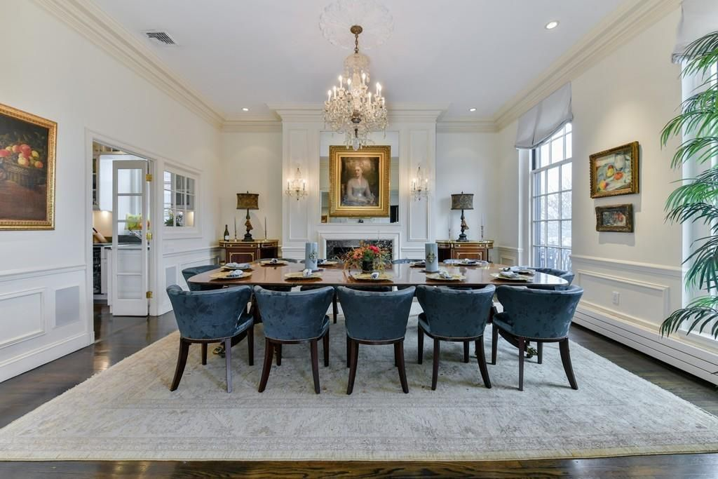 A large, opulent dining room with a 12-seat table and a fireplace.
