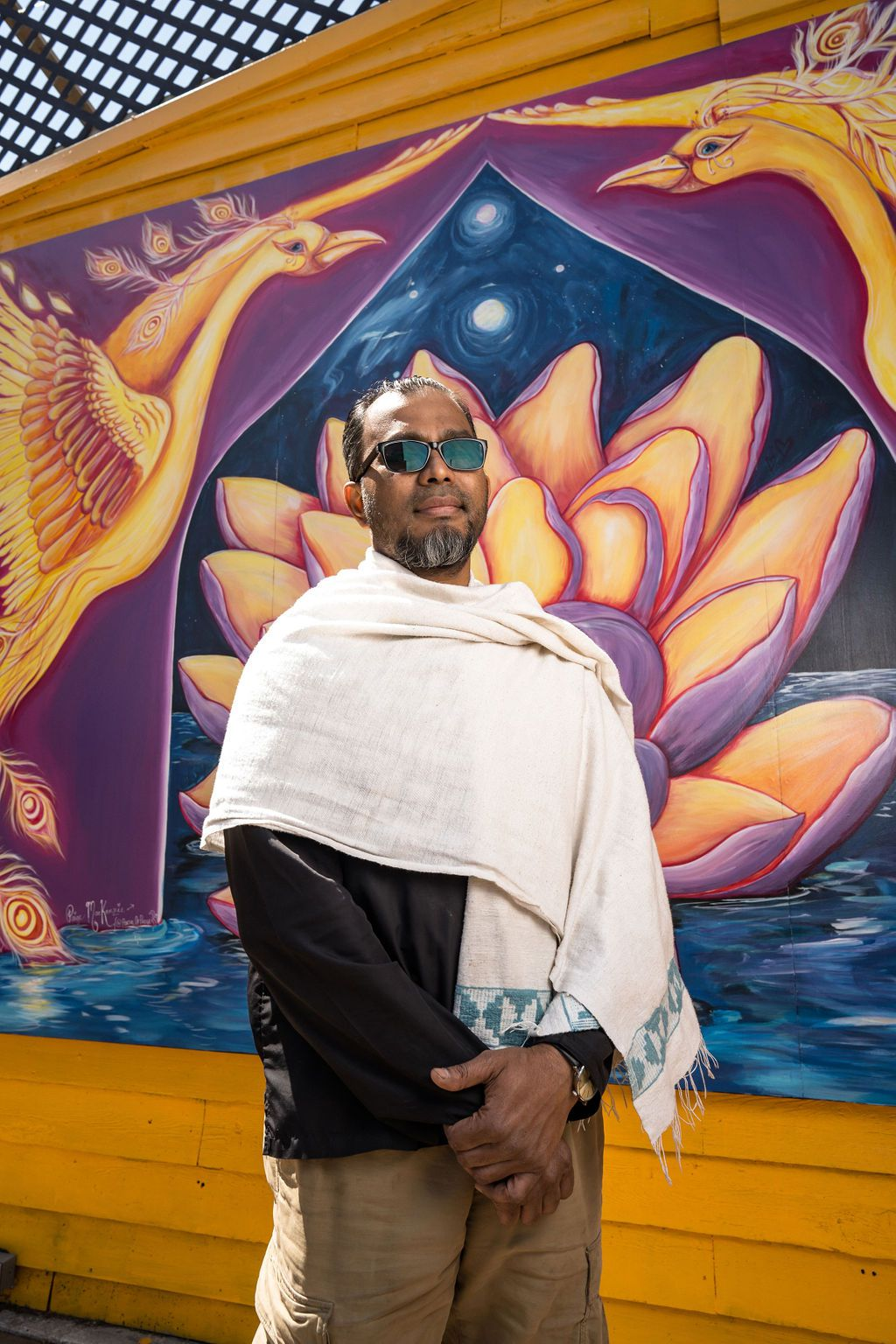 Man wearing sunglasses standing in front of a colorful mural.
