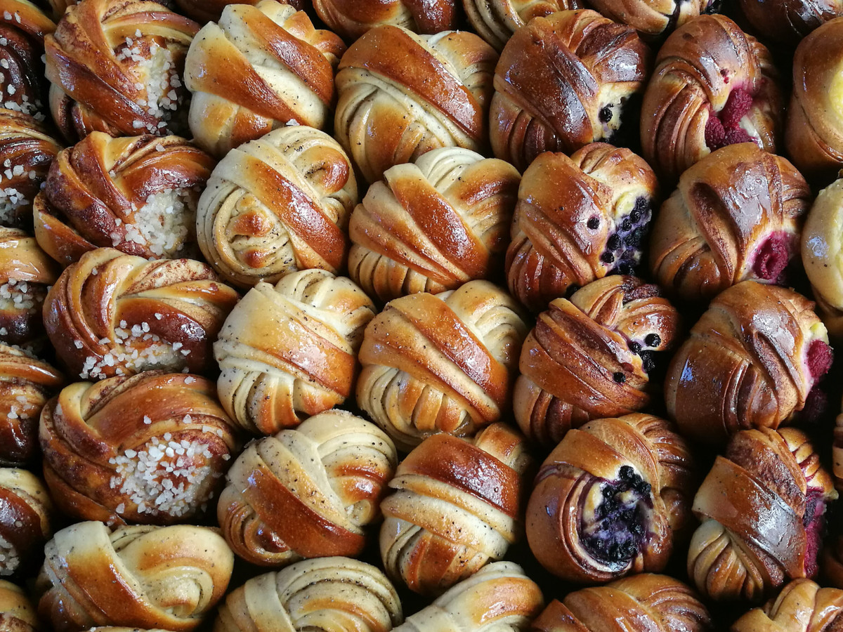 A tightly packed tray of knotted Scandinavian buns, with cardamom, cinnamon, vanilla, and raspberry