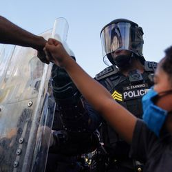 A protester fist bumps a police officer as a young boy raises his fist during a demonstration on May 31, 2020 in Atlanta, Georgia.