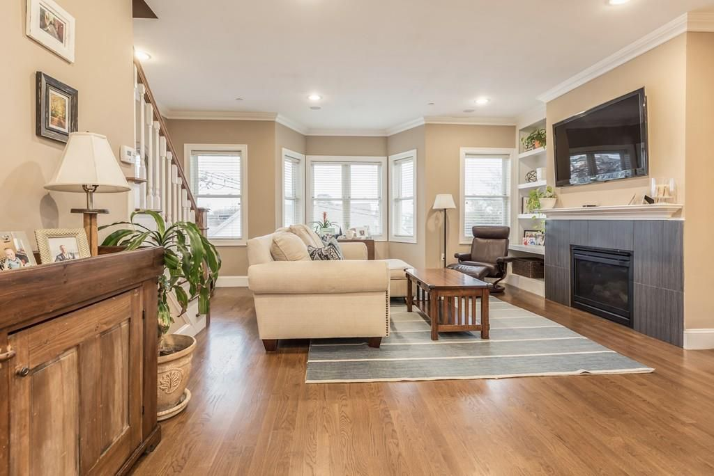 A spacious living room with a fireplace and furniture, and there's a stairwell leading down to it.