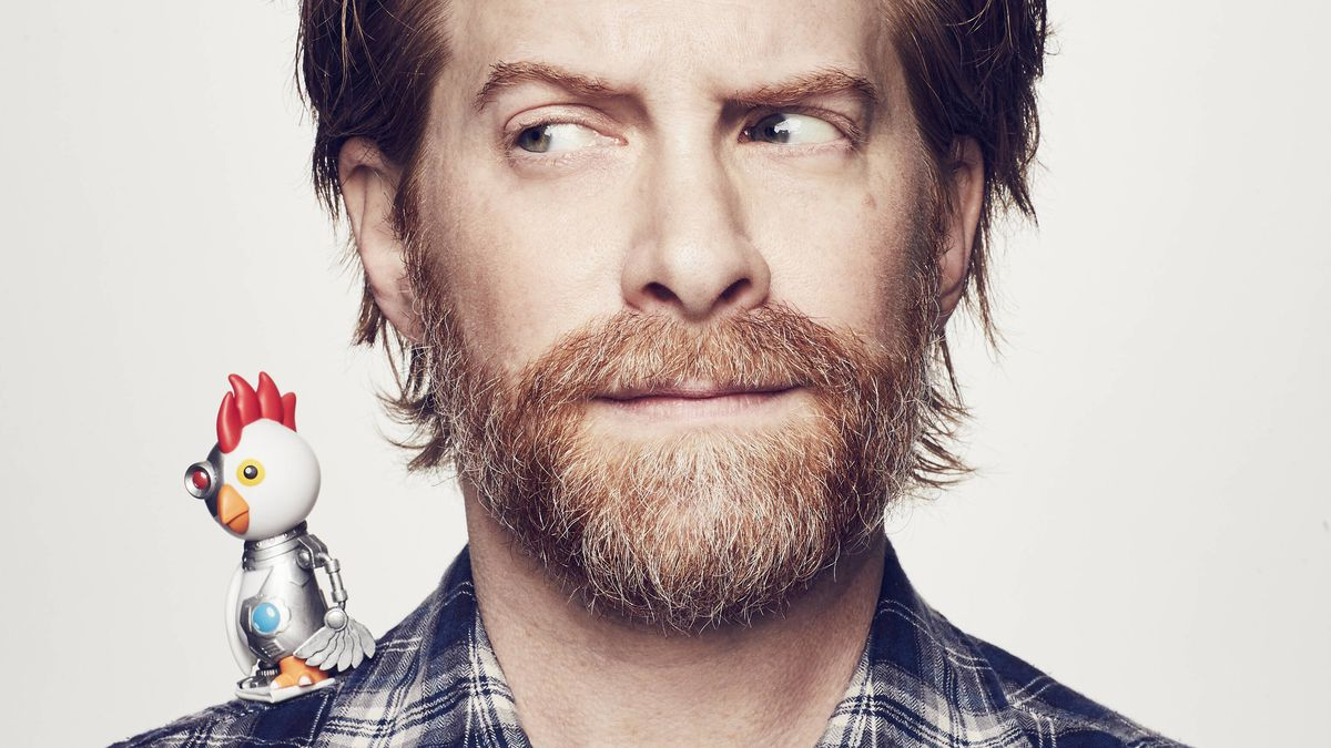 the robot chicken from robot chicken sits on the right shoulder of seth green, who is wary