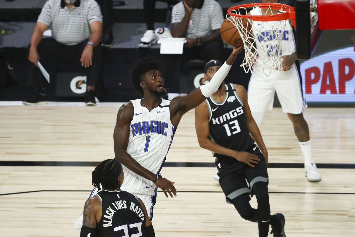 Jonathan Isaac of the Orlando Magic shoots the basketball against Richaun Holmes of the Sacramento Kings and guard Corey Brewer in the first half of a NBA basketball game at HP Field House at ESPN Wide World Of Sports Complex on August 2, 2020 in Lake Buena Vista, Florida.