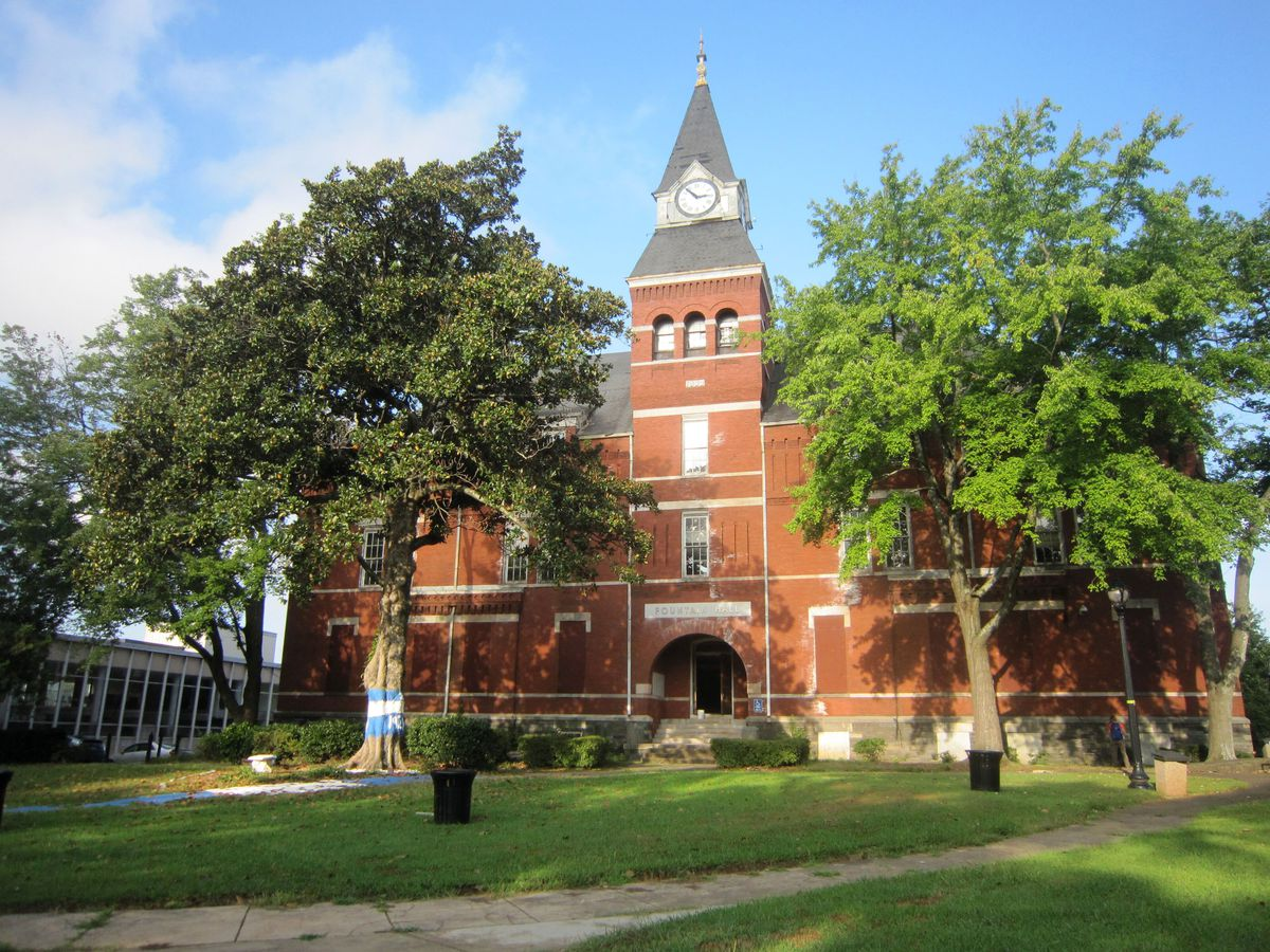 A large brick building with a pointed clock tower that's boarded up.