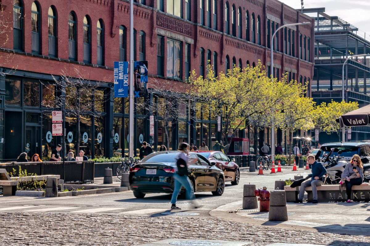 An intersection with cobblestone, people sitting on a bench, a valet umbrella, and brick buildings.