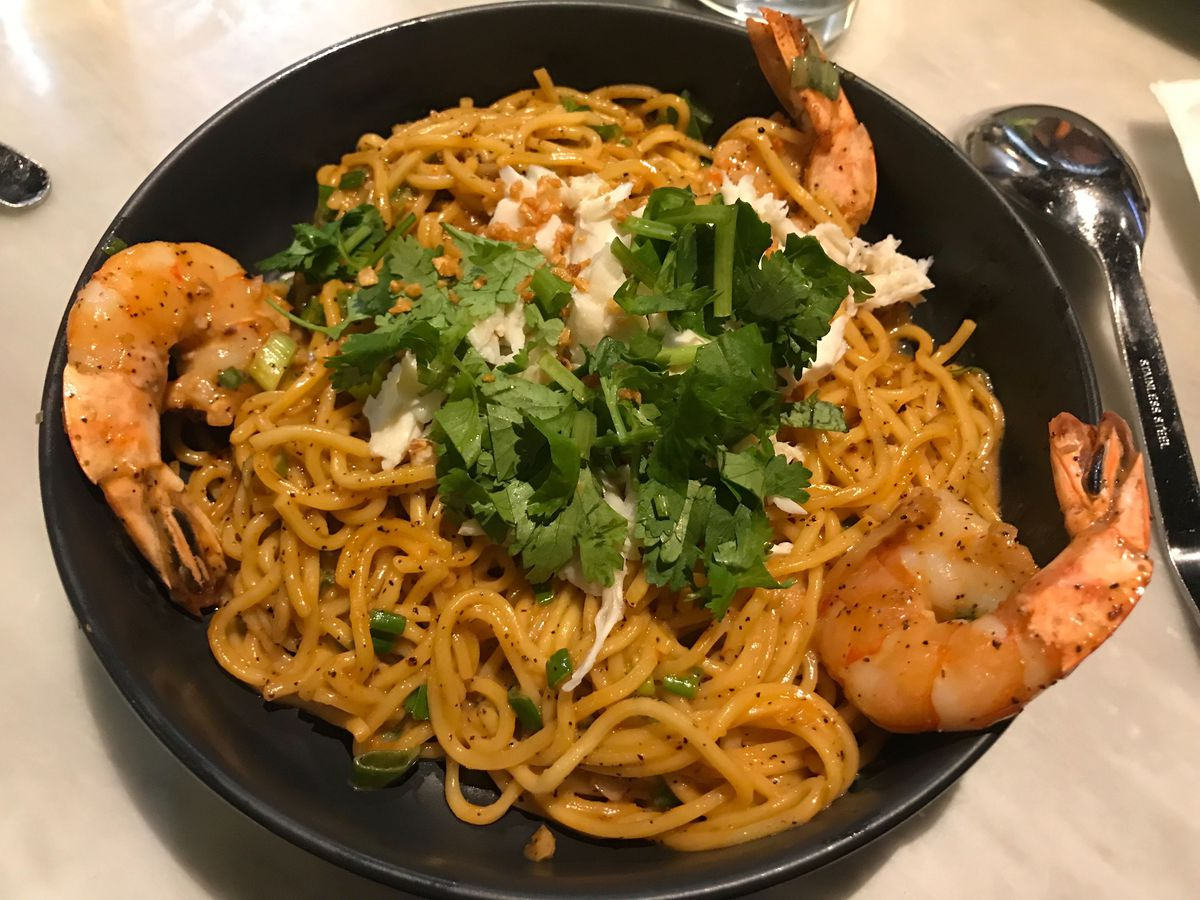 A black bowl filled with noodles, with three big shrimps sitting on opposite sides of the bowl
