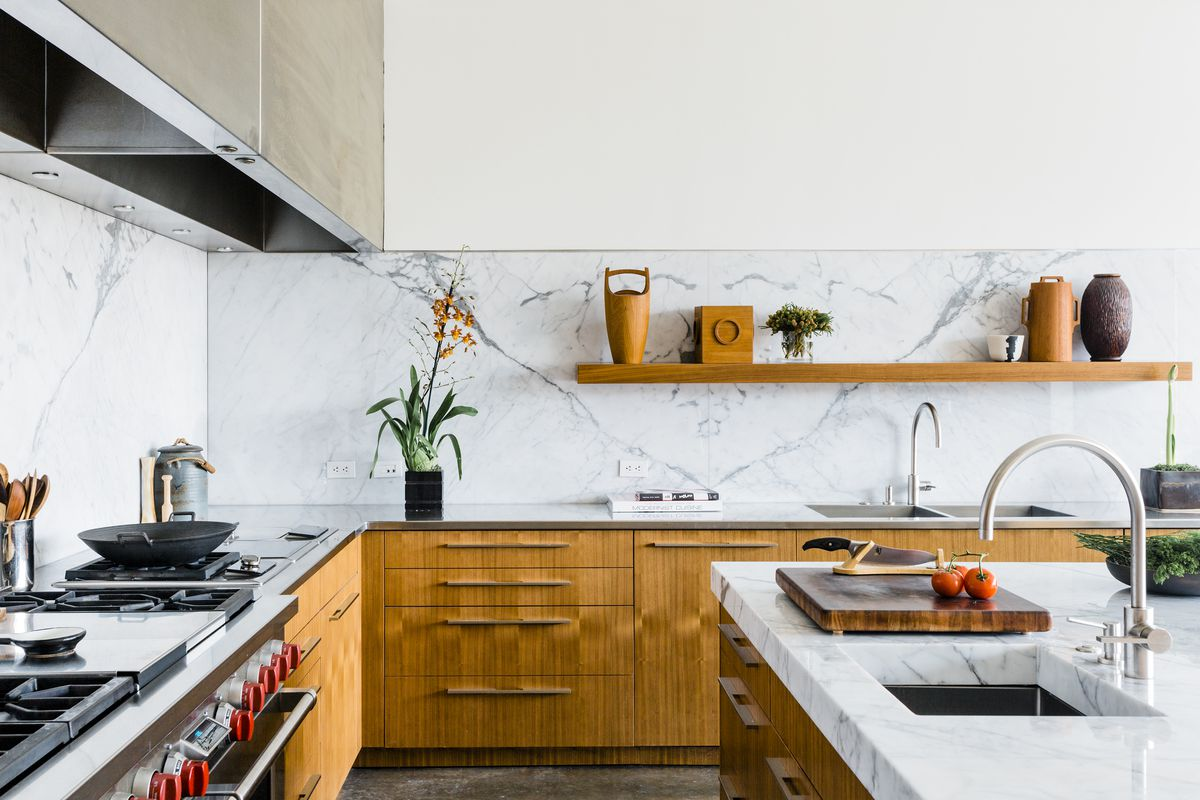 The kitchen has wood lower cabinets and a white marble backsplash and counters. A shelf holds decorative objects.