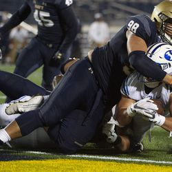 BYU running back Lopini Katoa dives fora touchdown as Navy guard Mike Flowers (98) defends during the first half of an NCAA college football game, Monday, Sept. 7, 2020, in Annapolis, Md.
