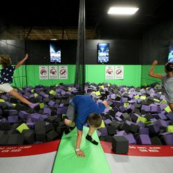 Bridger Harward, center, climbs out of a foam pit as Julia Rossiter, left, and Emory King, right, jump in at Get Air Salt Lake in Murray on Friday, July 29, 2016.