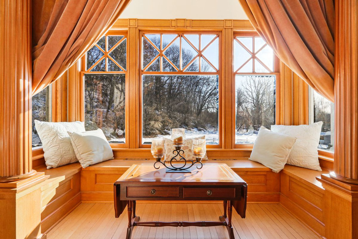 A bay window area has wooden benches, wood trim, a coffee table, and pillows.