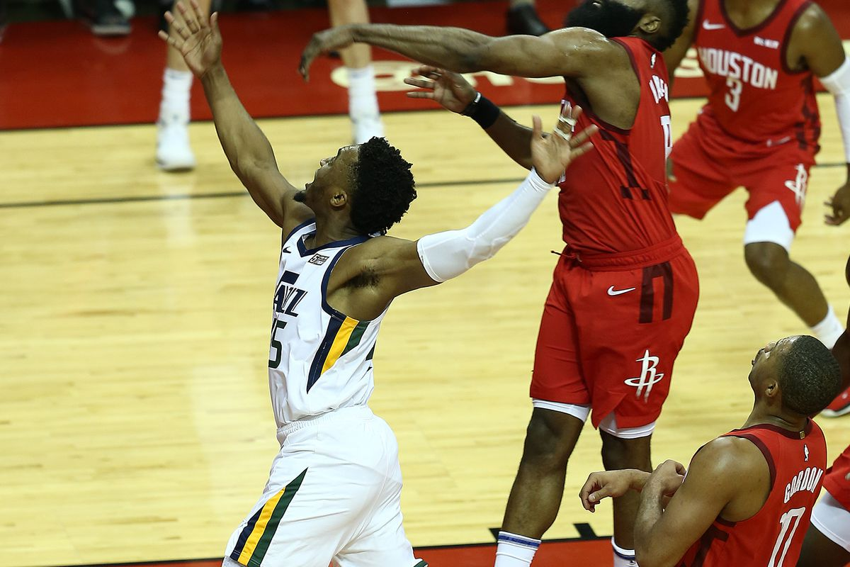 Houston Rockets guard James Harden (13) blocks a shot attempt by Utah Jazz guard Donovan Mitchell (45) as the Utah Jazz and the Houston Rockets play game one of their series in the NBA playoffs at the Toyota Center in Houston on Sunday, April 14, 2019.