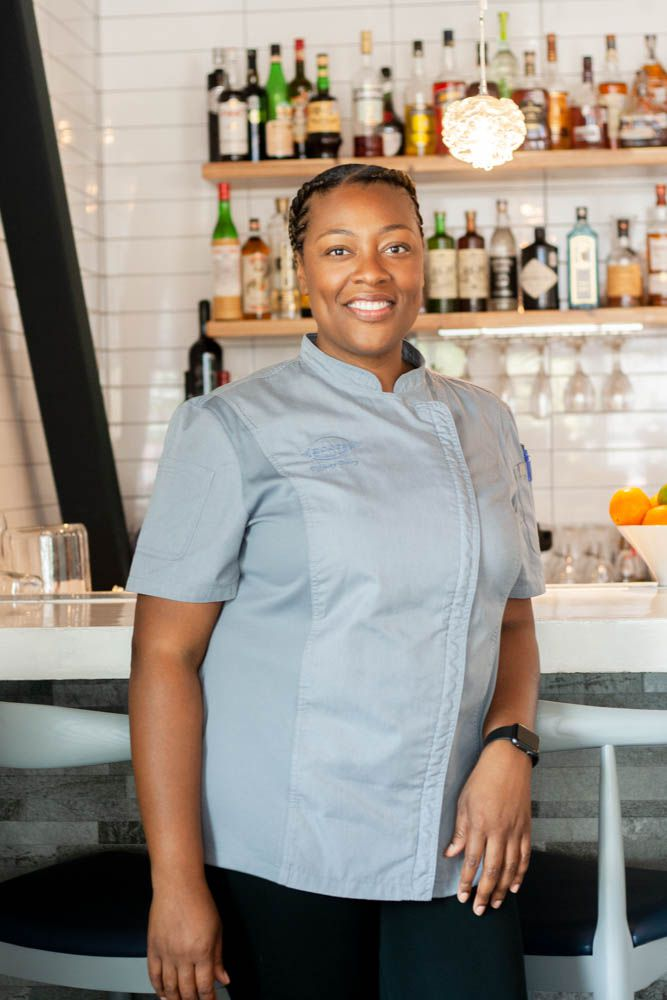 Chef Tiffany Derry, a Black woman, stands in a blue chef's coat and black pants in front of a bar. The white wall behind her is lined with liquor bottles.