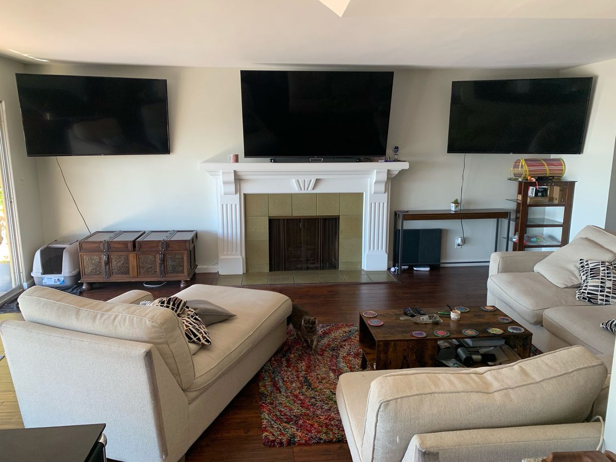 a photo of a living room with three TVs mounted on a wall above a fireplace