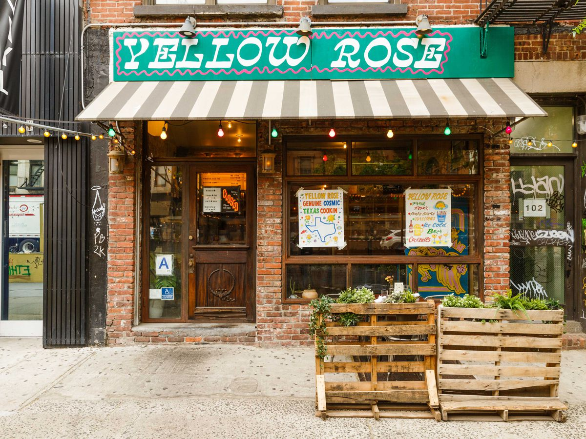 The sign for Yellow Rose, a mix of white lettering, pink bordering, and a teal background hangs above the striped awning of the venue