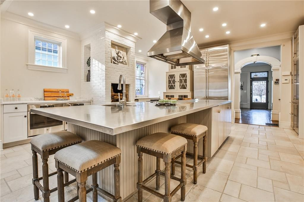 A large white kitchen with a huge range hood.