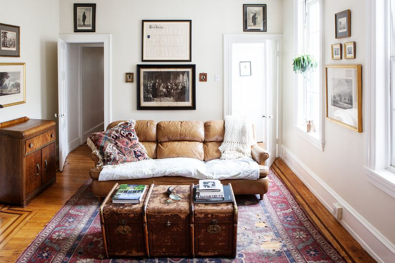 A light brown leather chair in the center of a sunny living room. In front of it sits an old wooden trunk serving as a coffee table.