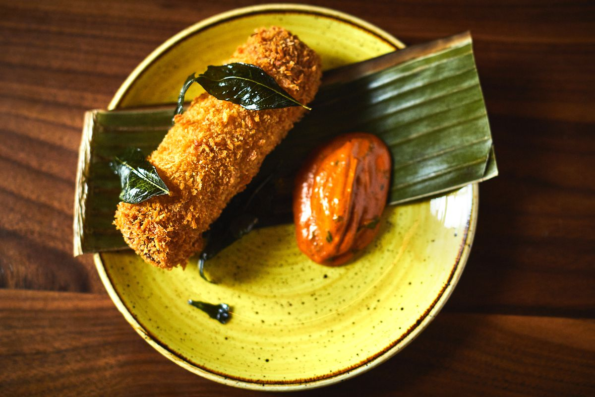 A mutton roll with curry leaf and tomato on a yellow plate.