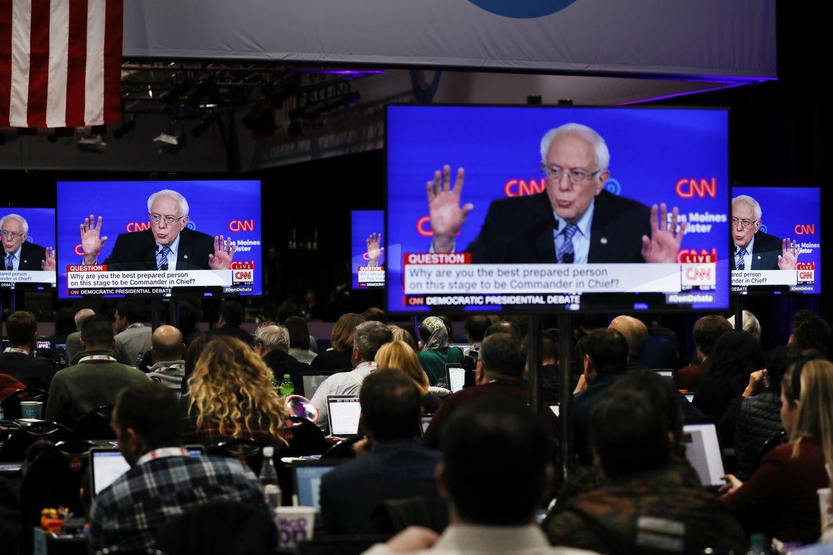 Bernie Sanders on a television screen on the debate stage as people look on.