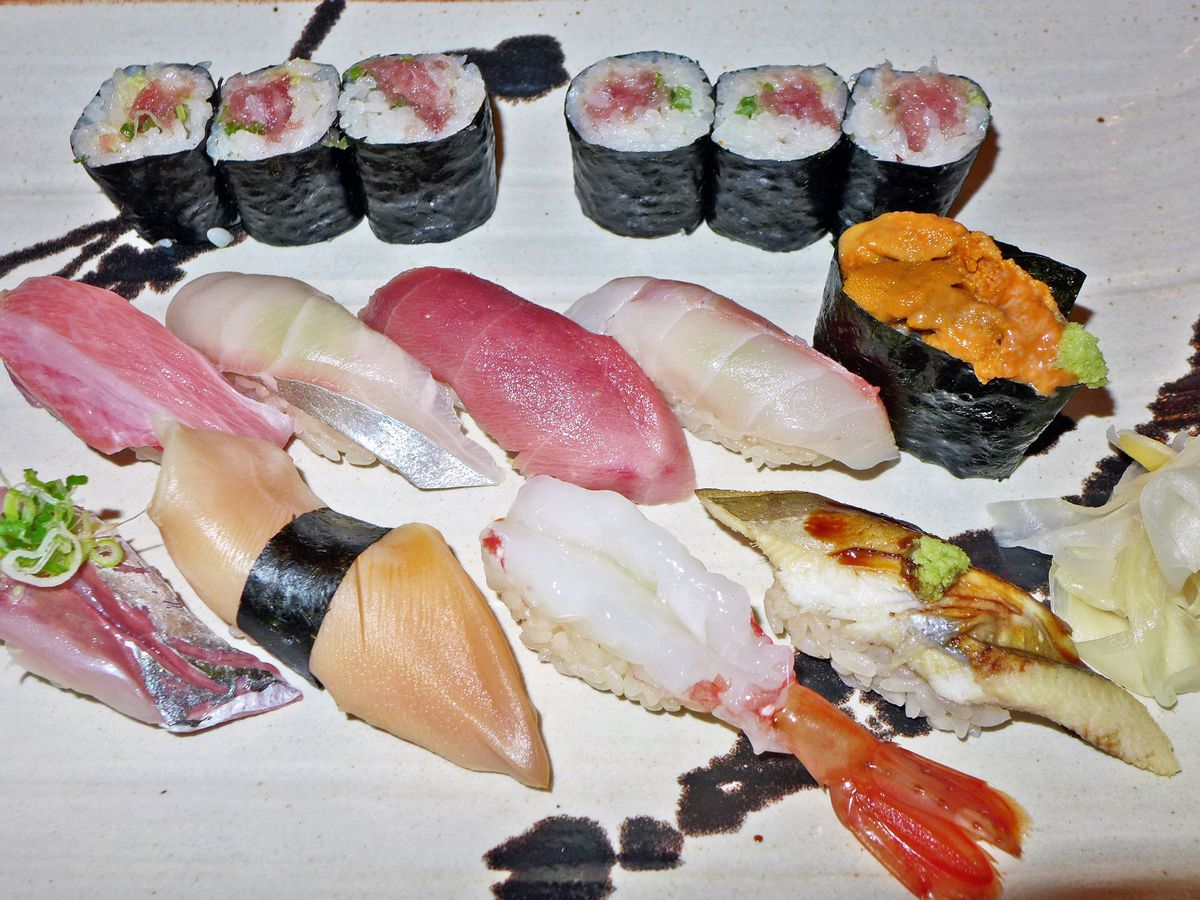 A luscious plate of sushi, totally filling the frame, with orange sea urchin, pink tuna, and many other fish on rice, some with roe.