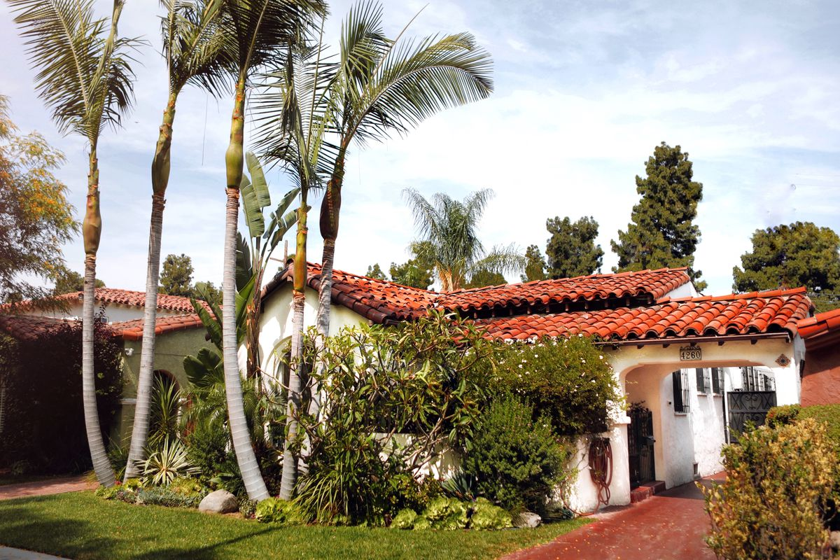 Tile-roofed home surrounded by palm trees.