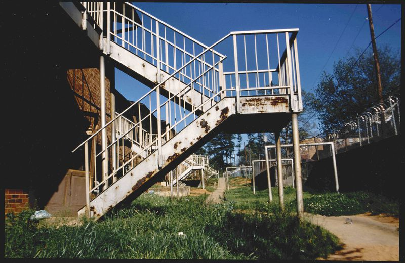 Rusted white apartment stairs with high grass and large section of dry dirt close to the barbwire fence. Square metal beams in the middleground along with stairs leading to other apartments. Trees and powerlines in the background.
