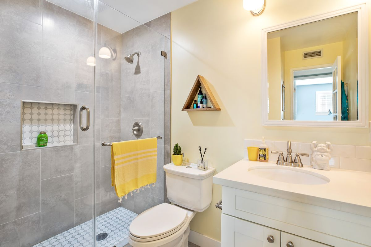 A bathroom with a glass shower enclosure and a single-vanity sink.