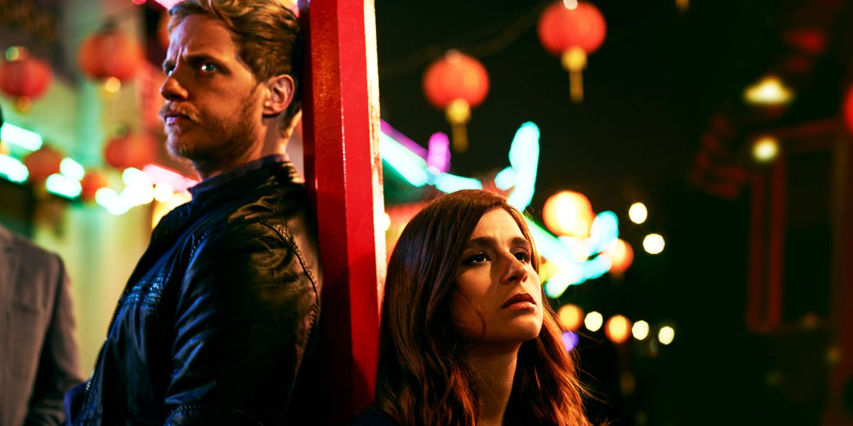 Jimmy and Gretchen stand back-to-back on a dark street, lit by colorful lamps.