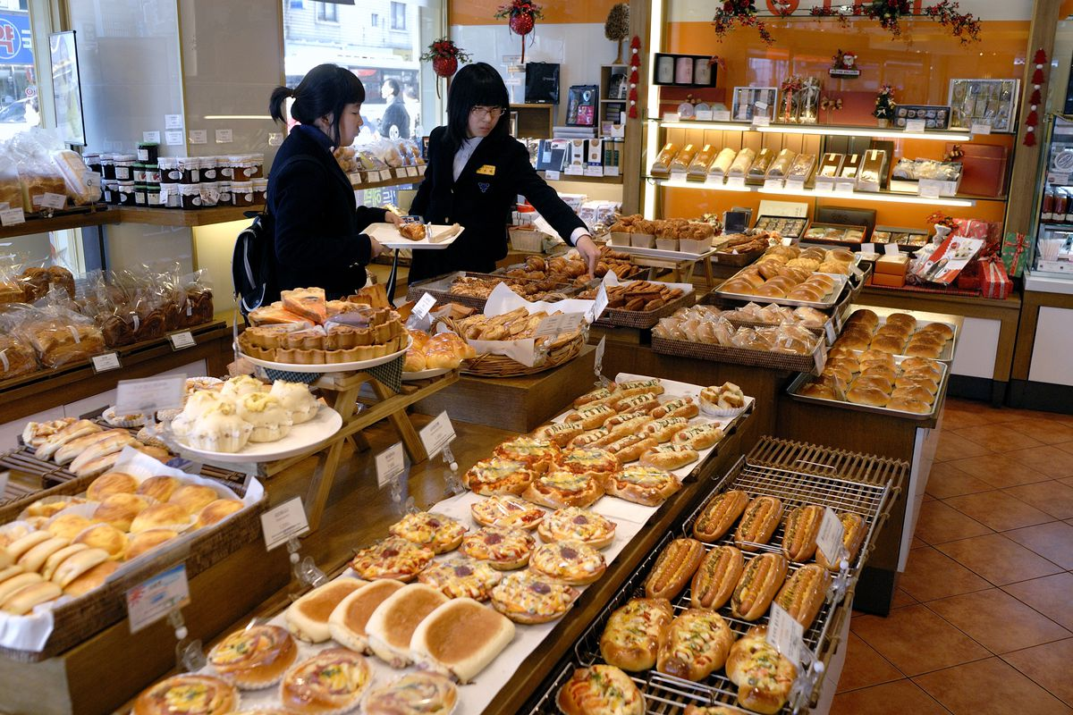 Two people picking out treats inside a Paris Baguette