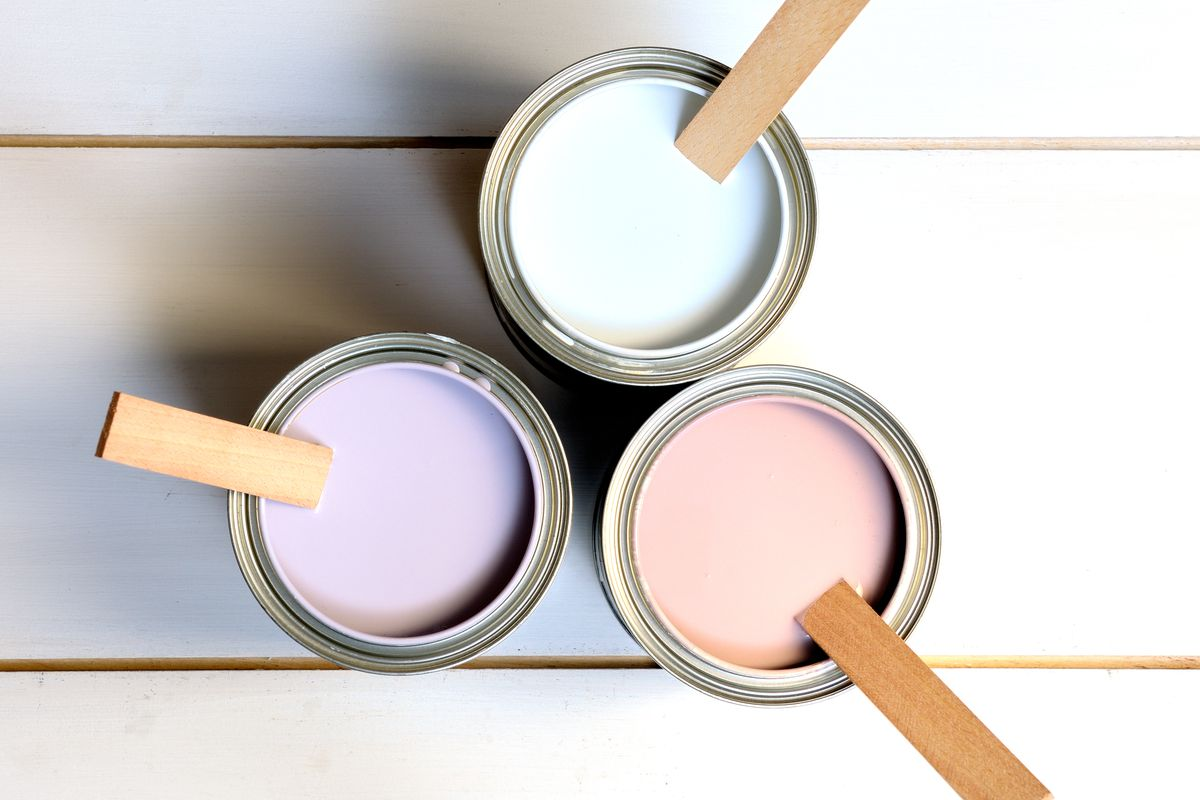 Cans of paint with mixing sticks.