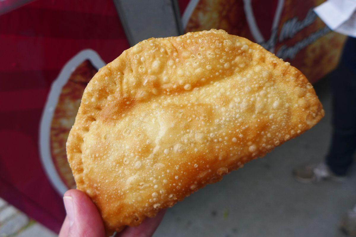 A hand holds a half moon shaped empanada.