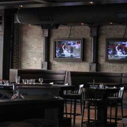 The main dining area with high tops, booths and TVs