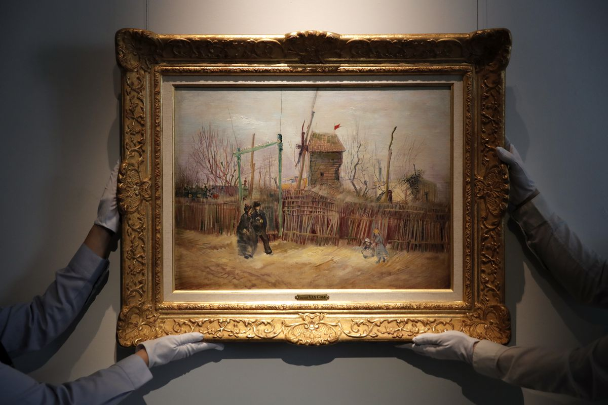 In this Feb. 25, 2021, file photo, Sotheby's personnel display Scene de rue à Montmartre (Street scene in Montmartre), a painting by Dutch master Vincent van Gogh at Sotheby's auction house in Paris.