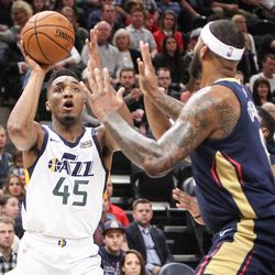 Utah Jazz guard Donovan Mitchell (45) pulls up and takes a shot against New Orleans Pelicans center DeMarcus Cousins (0) as Utah hosts New Orleans at Vivint Arena in Salt Lake on Friday, Dec. 1, 2017.