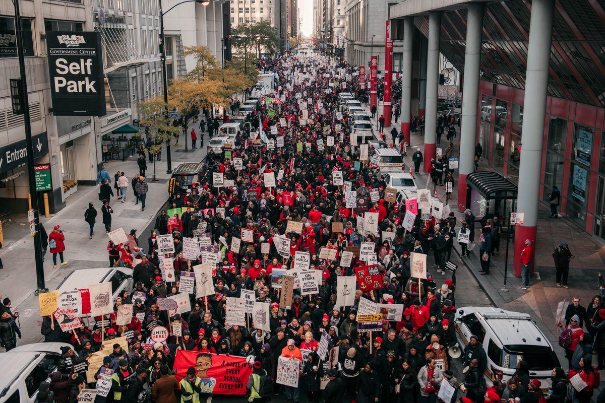 Chicago teachers march through a downtown street blocking car traffic.