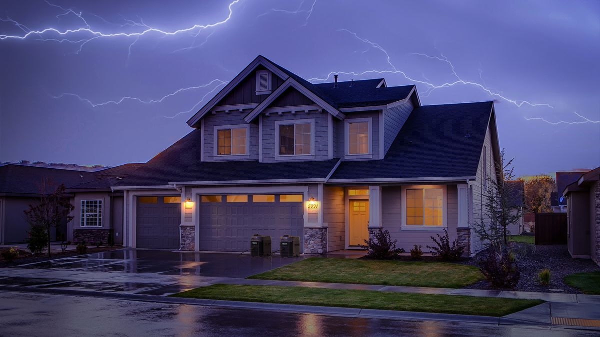 A two-story home has two portable power stations out front in the house's driveway. Several lights in the house are on, and water reflects the light on an asphalt road in front of the house. Lightning crosses a dark blue sky overhead.