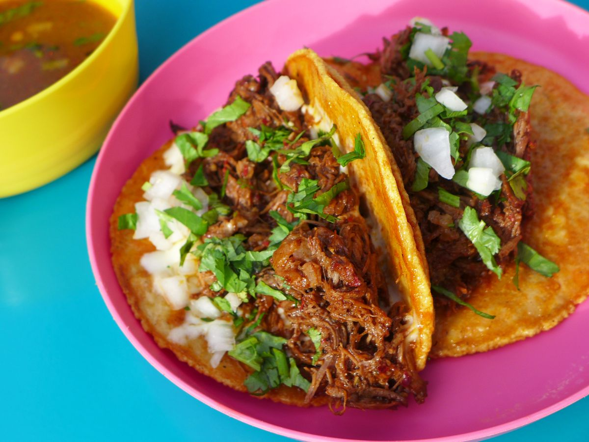 A pair of meat stuffed tacos on a pink plate with red soup on the side.